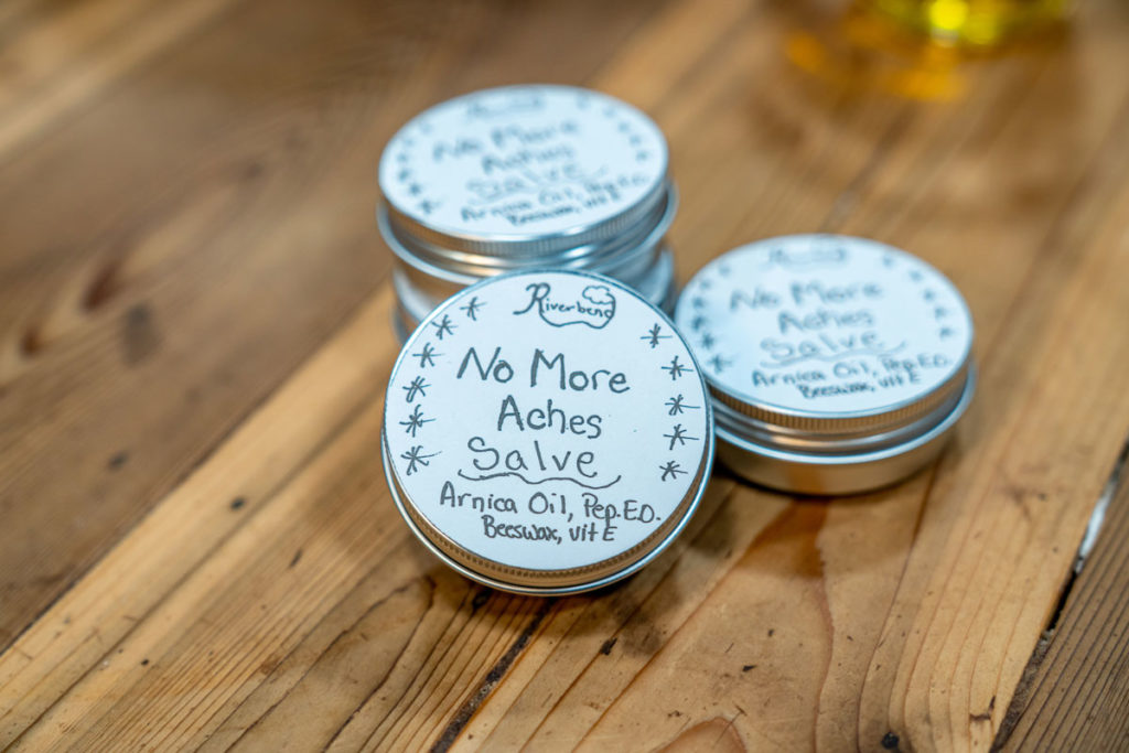 Four tins stacked of arnica salve.