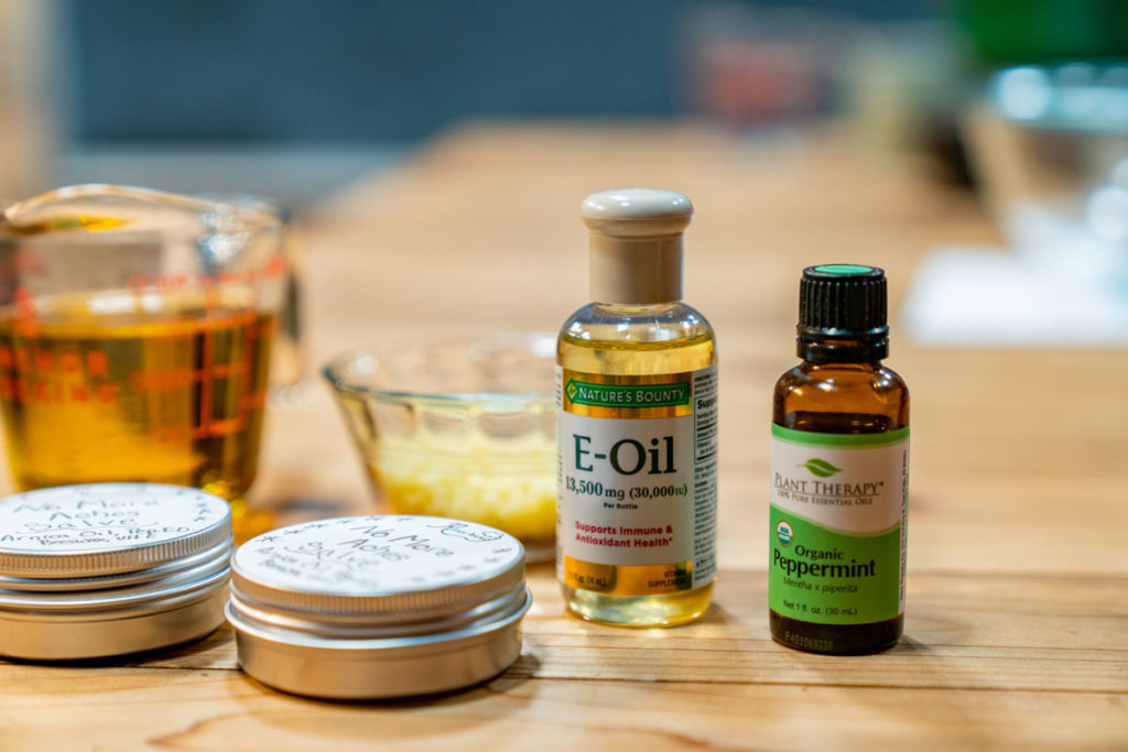 Ingredients for arnica salve on a wooden countertop.