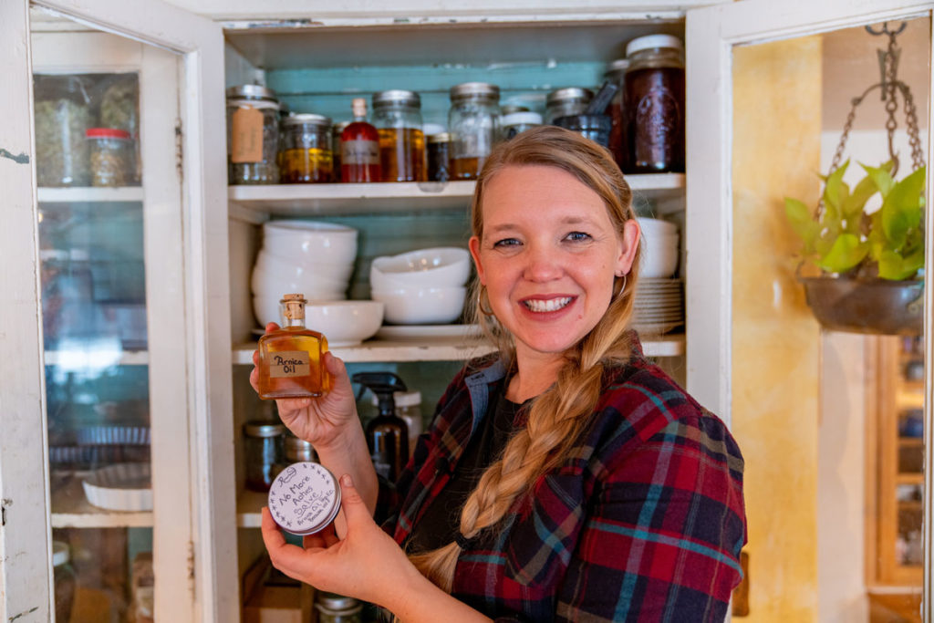 Woman standing in front of a hutch holding arnica oil and arnica salve.