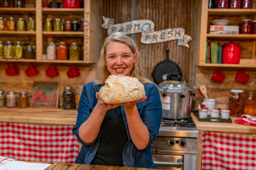 A woman holding up a loaf of fresh baked artisan bread.