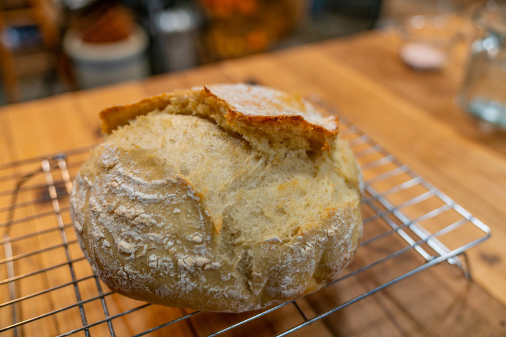 Loaf of artisan bread on a cooling rack.