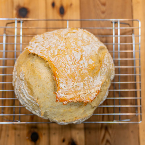 Vertical shot of a loaf of artisan bread on a cooling rack.