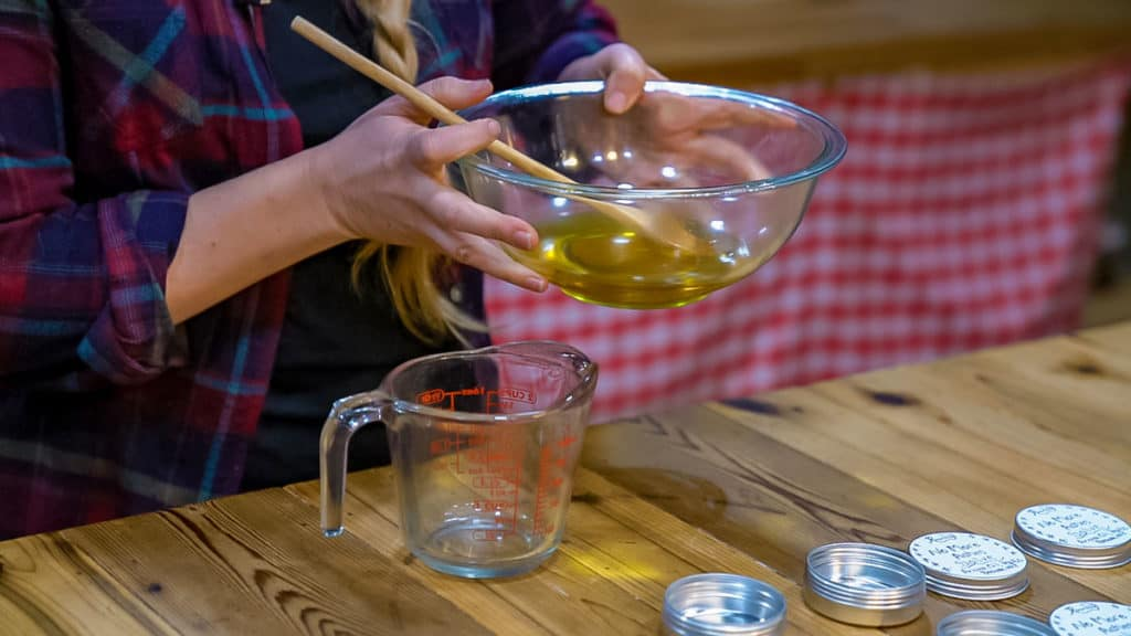 A woman pouring a bowl of liquid salve into a glass measuring cup.
