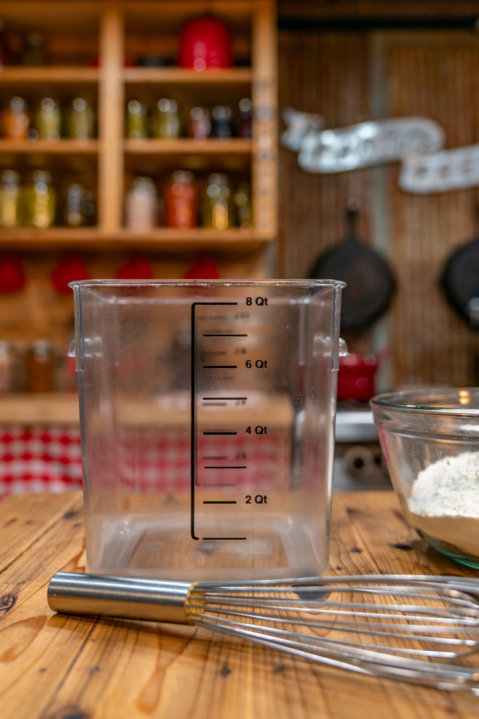 Food-grade storage bin and a whisk next to a bowl of flour for no-knead artisan bread.