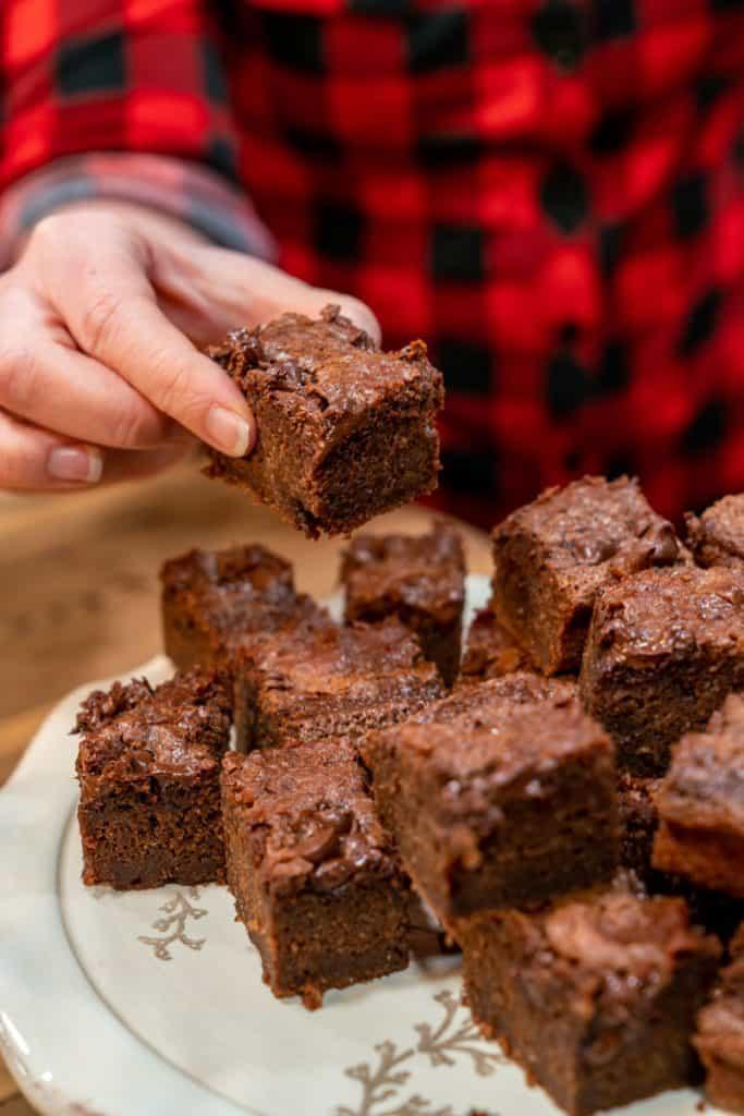 A hand picking up a sourdough brownie off a serving platter.