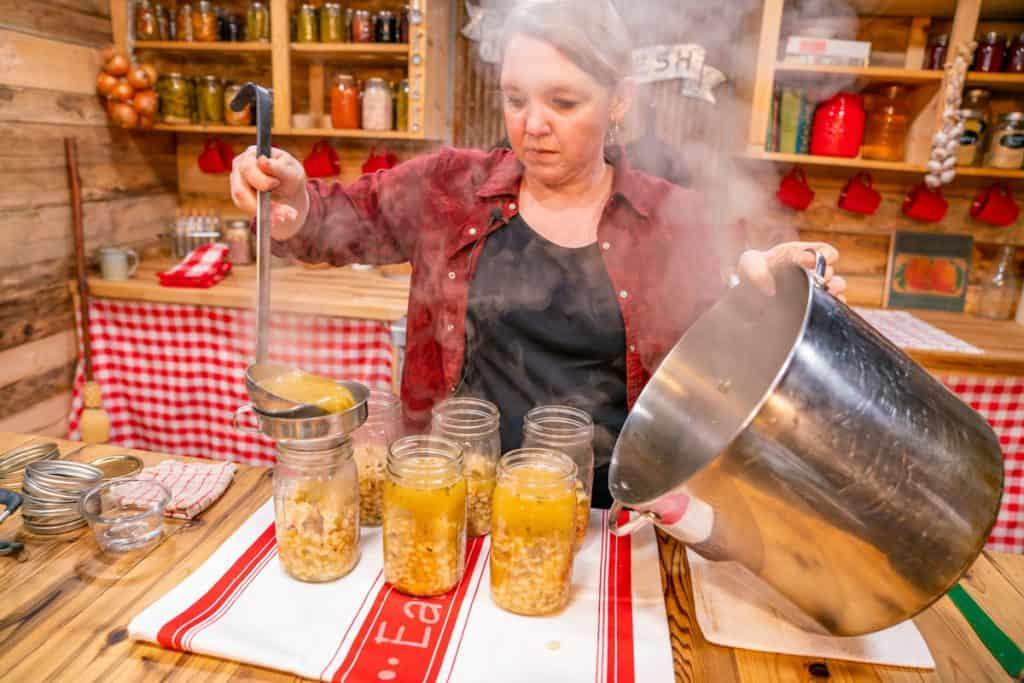 A woman ladling chicken chili into mason jars.