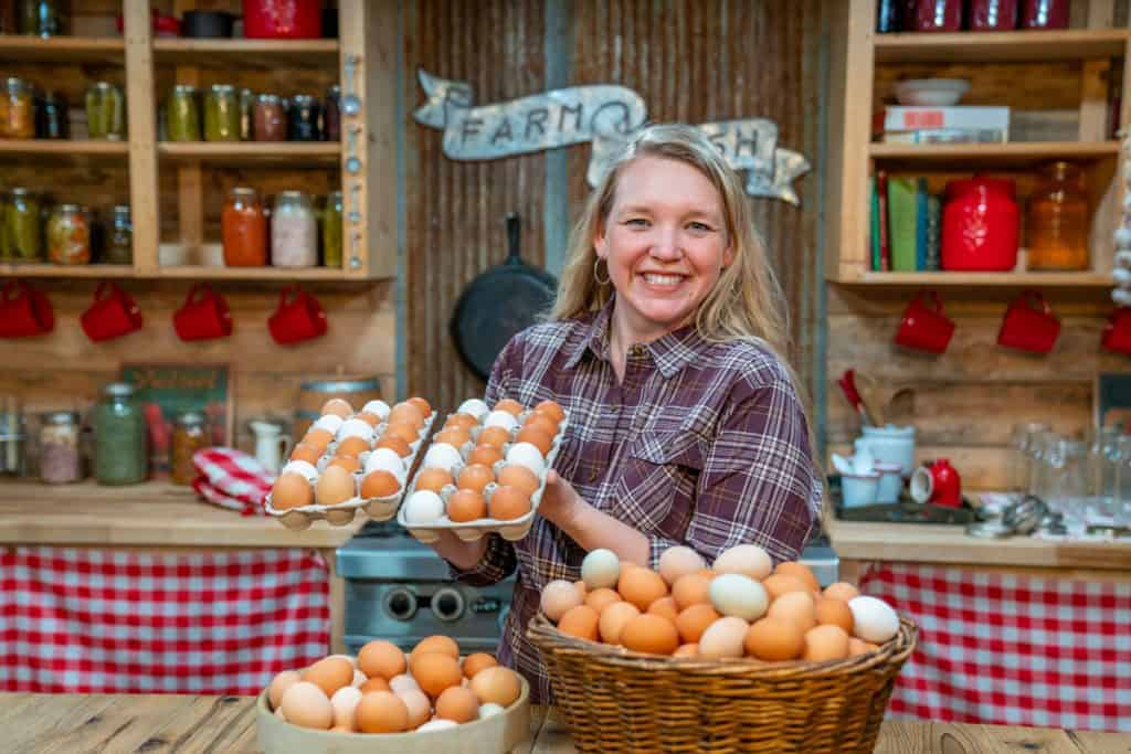 A woman standing in the kitchen with dozens of farm fresh eggs.