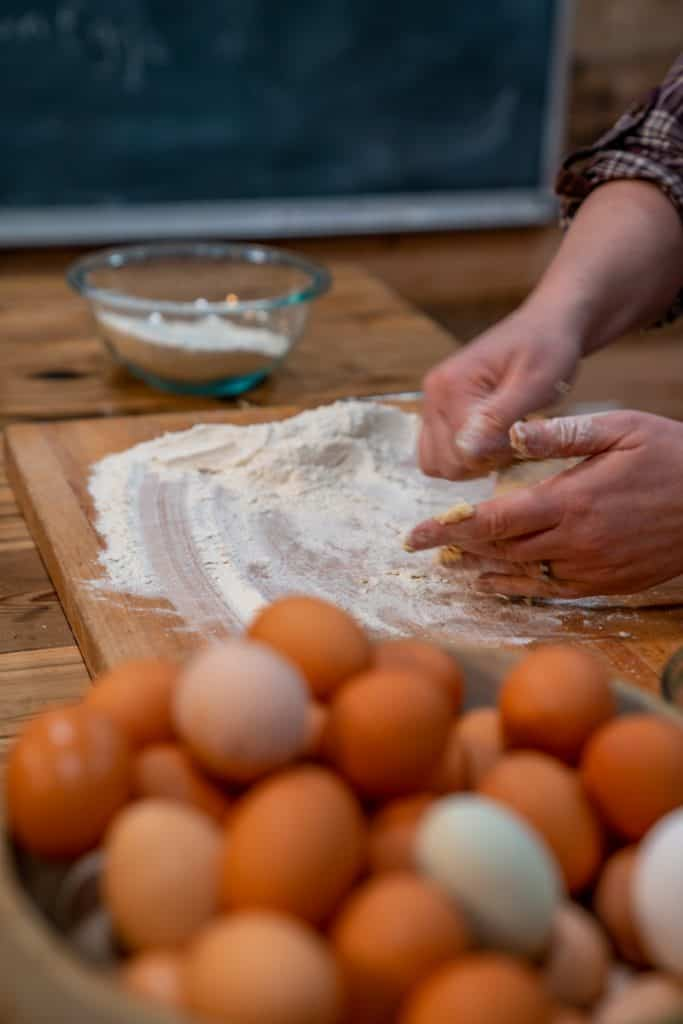 A woman mixing eggs into flour for egg noodles.