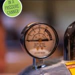 Pinterest pin for how to can broth with an image of the dial gauge of a pressure canner.