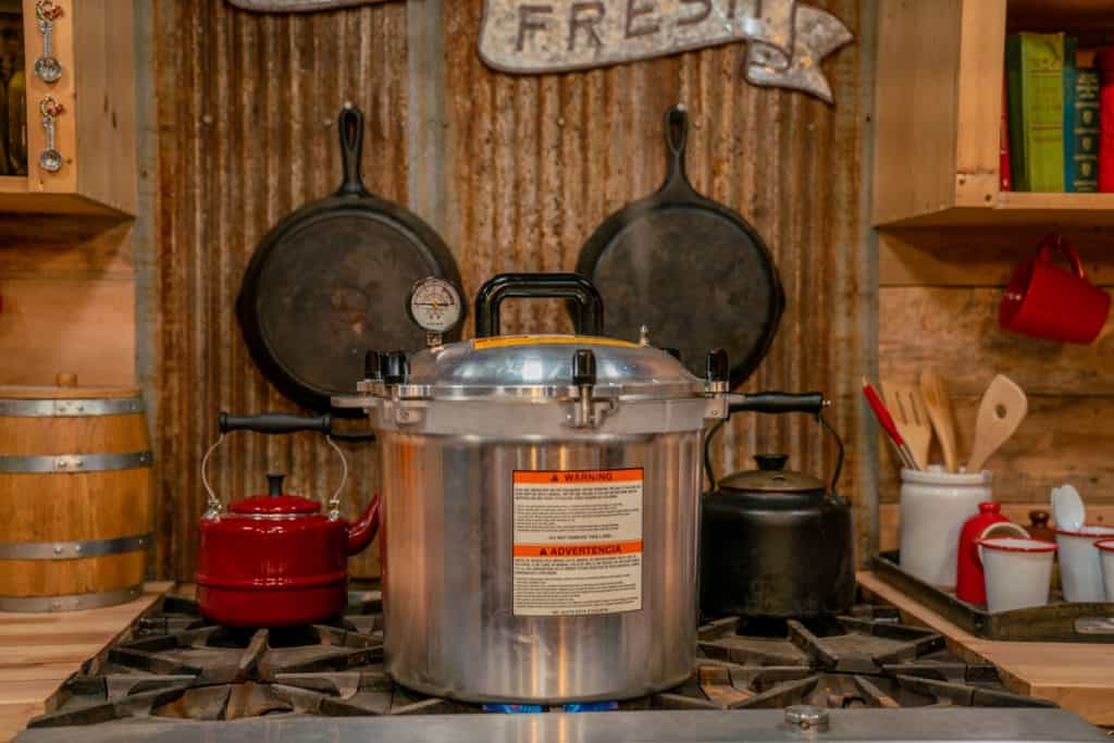 Photo of an all American pressure canner sitting on a gas stove.