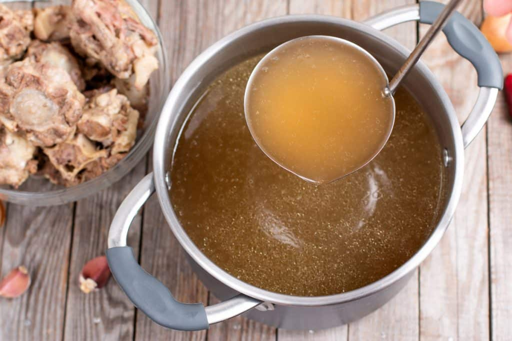 A ladle scooping broth out of a pot.