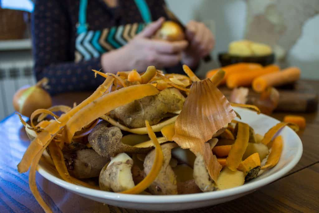 A plate of vegetable scraps on a table with a woman in the background peeling vegetables.