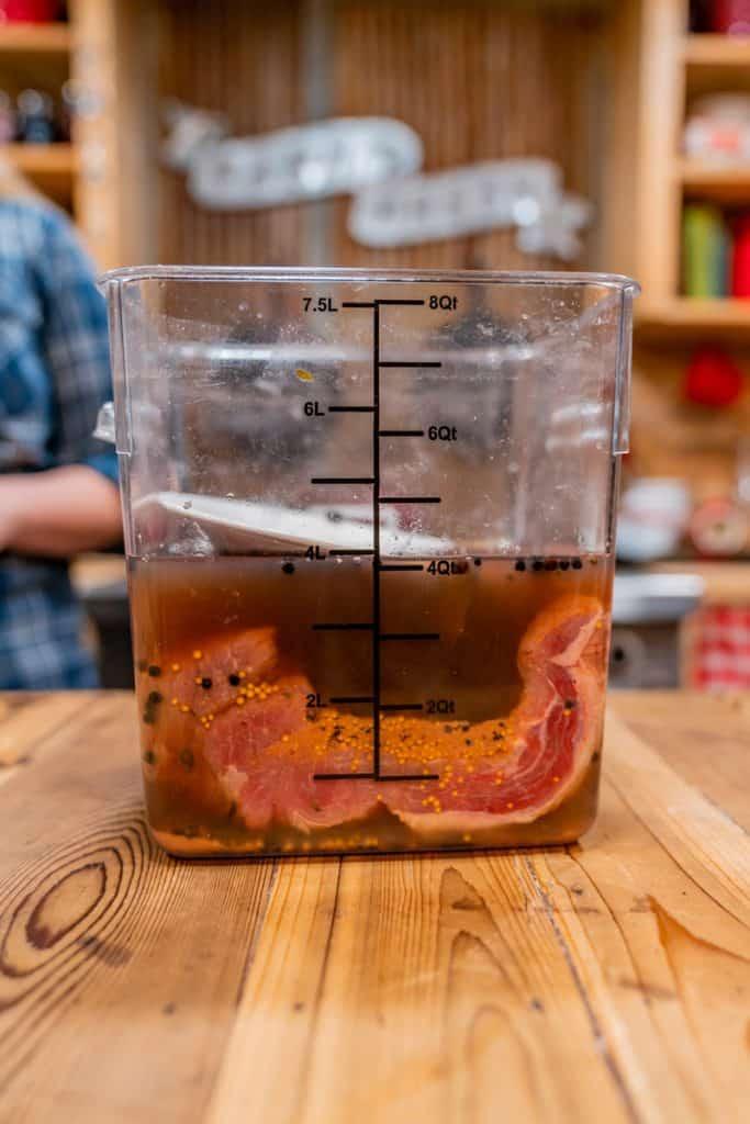 A beef brisket inside a food-grade bucket soaking in a brining liquid.