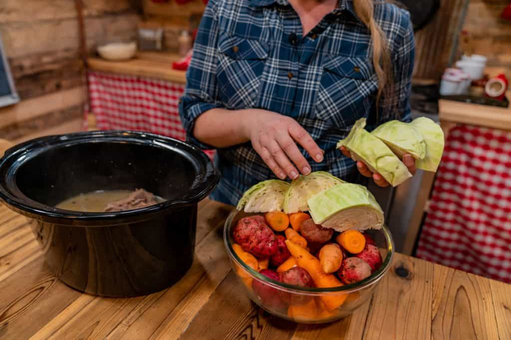 A woman adding fresh potatoes, carrots and cabbage to a crockpot with a corned beef brisket.
