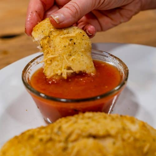 A parmesan garlic roll dipped into a bowl of marinara sauce.