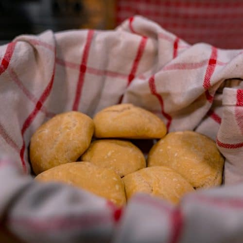 A basket with a red and white checkered towel filled with rolls.