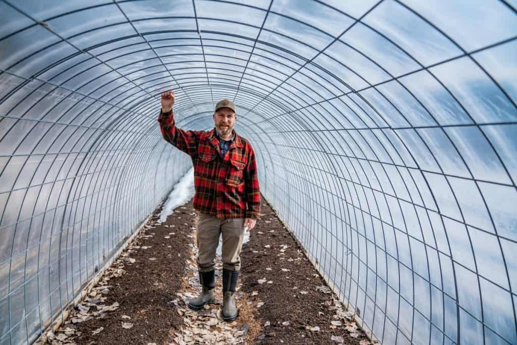 A man standing inside a completed 60 foot long hoop house.