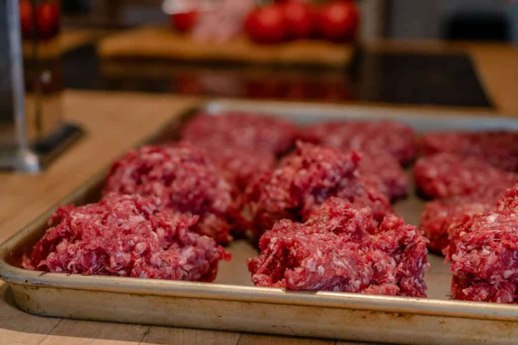 Ground beef patties on a cookie sheet.