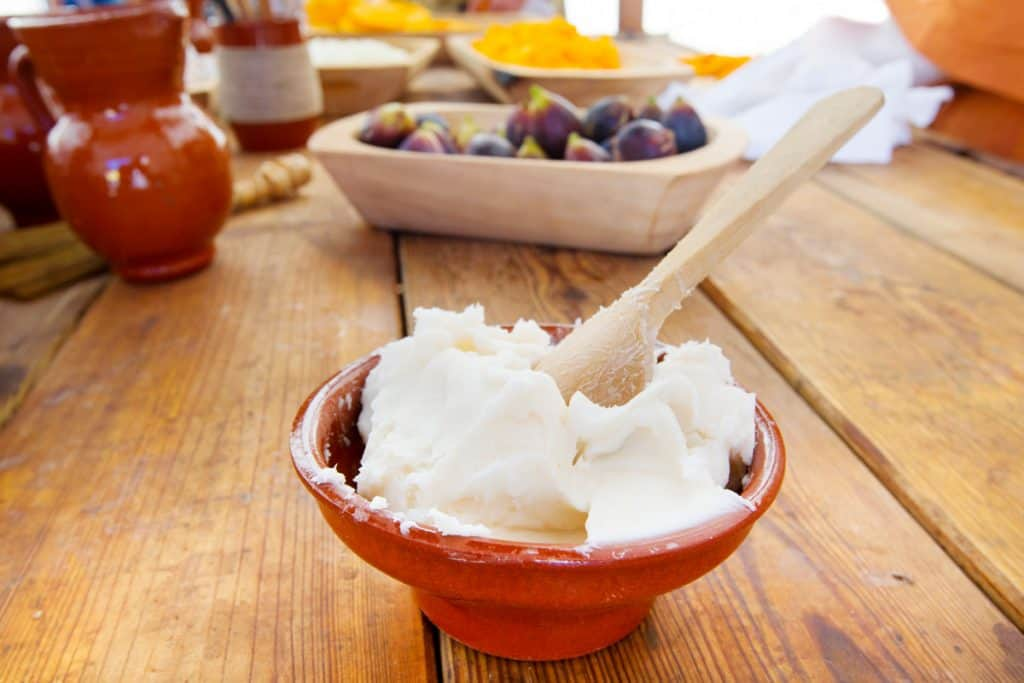 Lard in a bowl with a wooden spoon sitting on a kitchen counter.