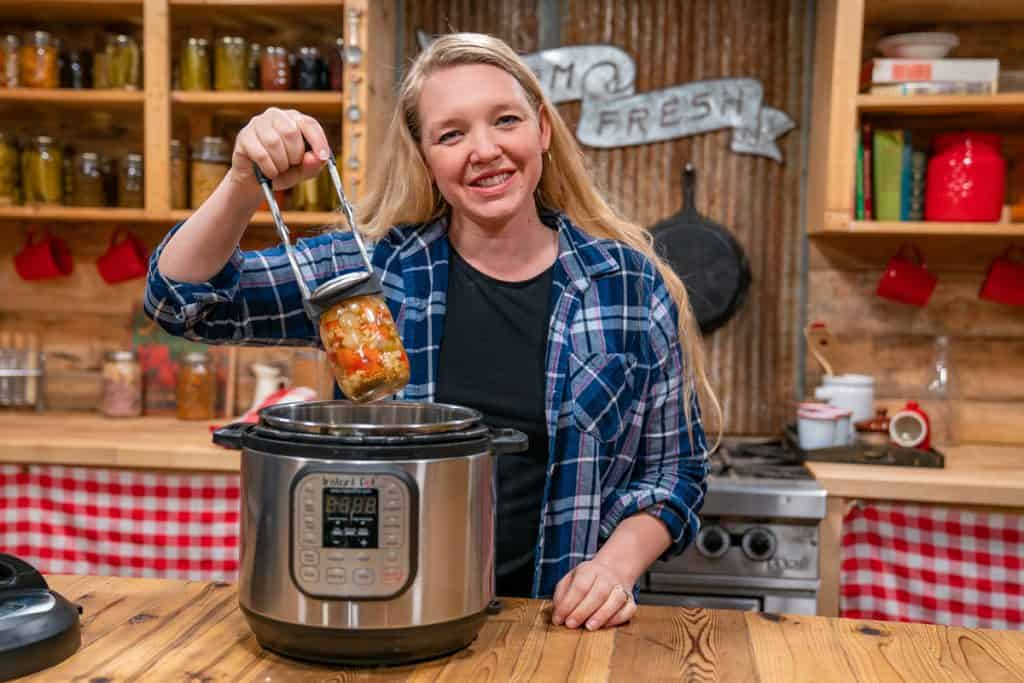 A woman pulling a jar out of the Instant Pot.