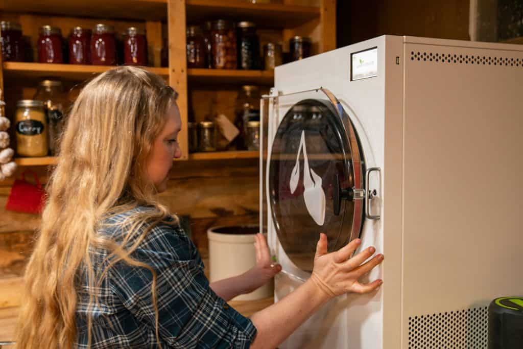 A woman closing the door to a Harvest Right freeze dryer.