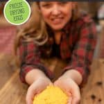 Pinterest pin for freeze dried eggs. Image of a woman holding a handful of powdered freeze dried eggs.