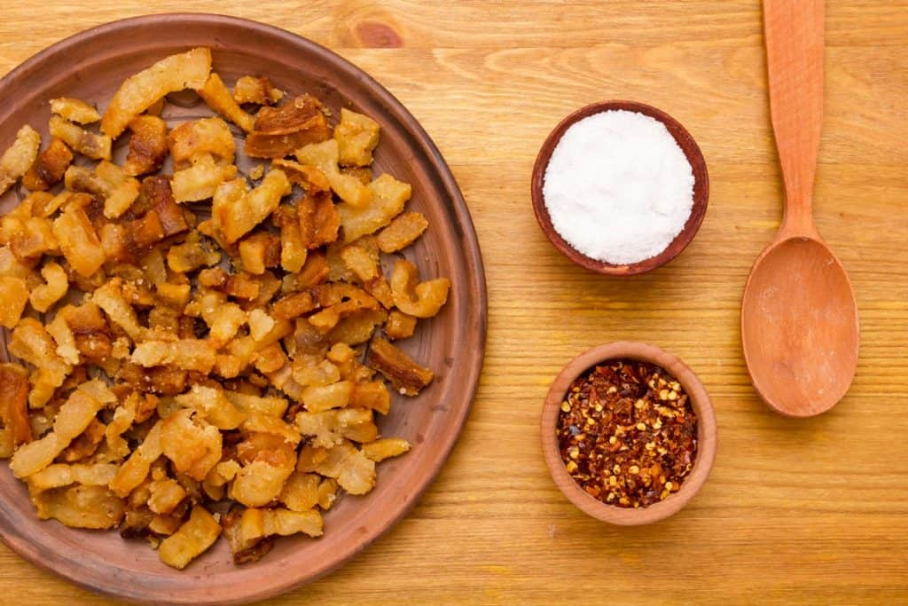 Cracklings sitting on a brown plate with two small bowls of salt and red pepper flakes beside it.