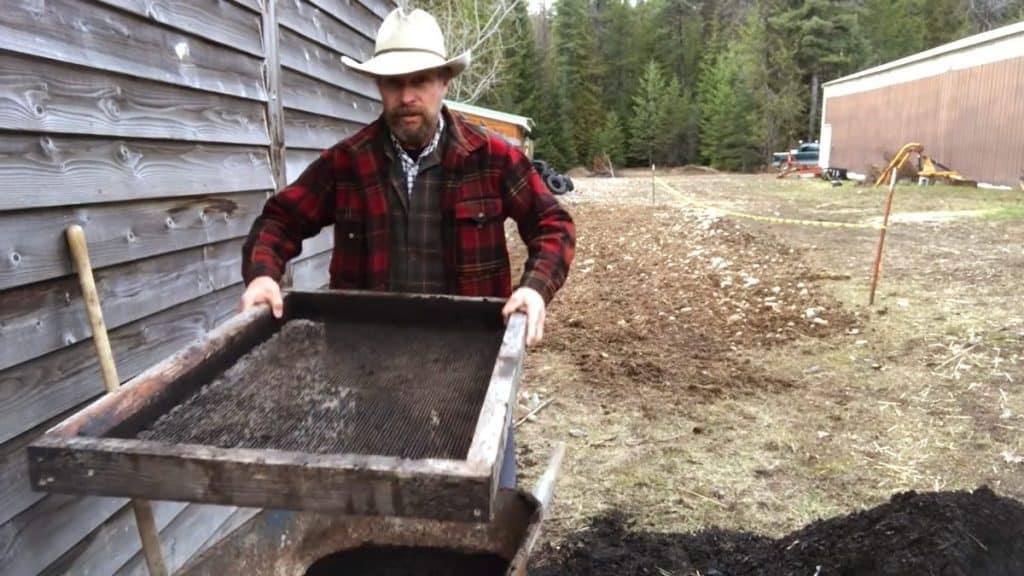 A man holding a compost sifter over a wheelbarrow.