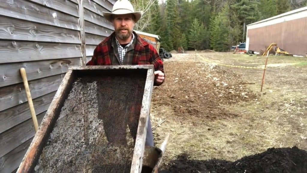 A man holding up one side of a compost sifter.