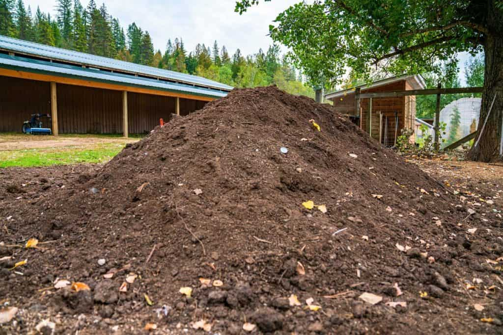 A large pile of compost with a barn in the background.