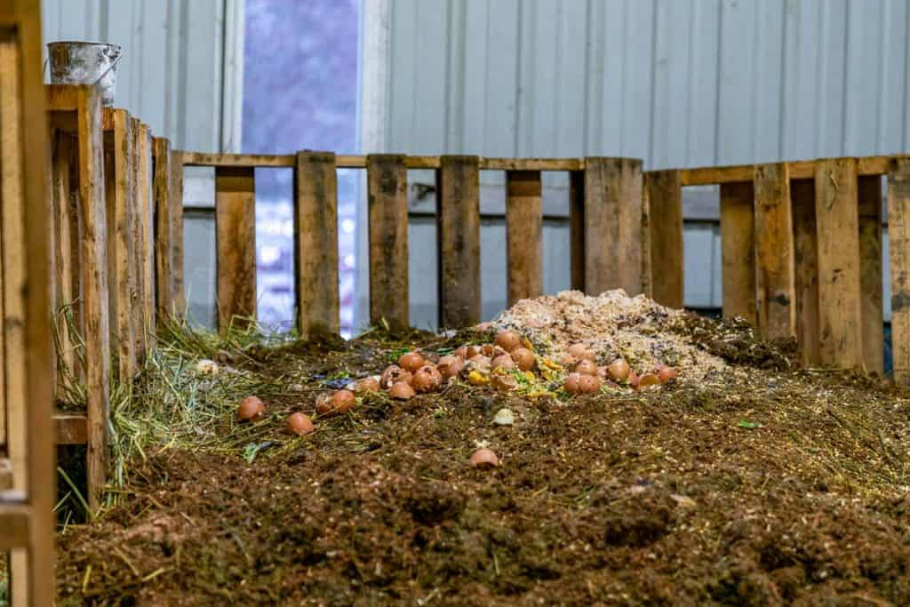 A large compost pile inside a barn.