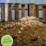 Pinterest pin for a DIY Compost Sifter or soil sifter. An image of a large pile of compost.