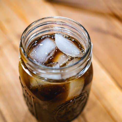 A mason jar filled with ice and homemade switchel.