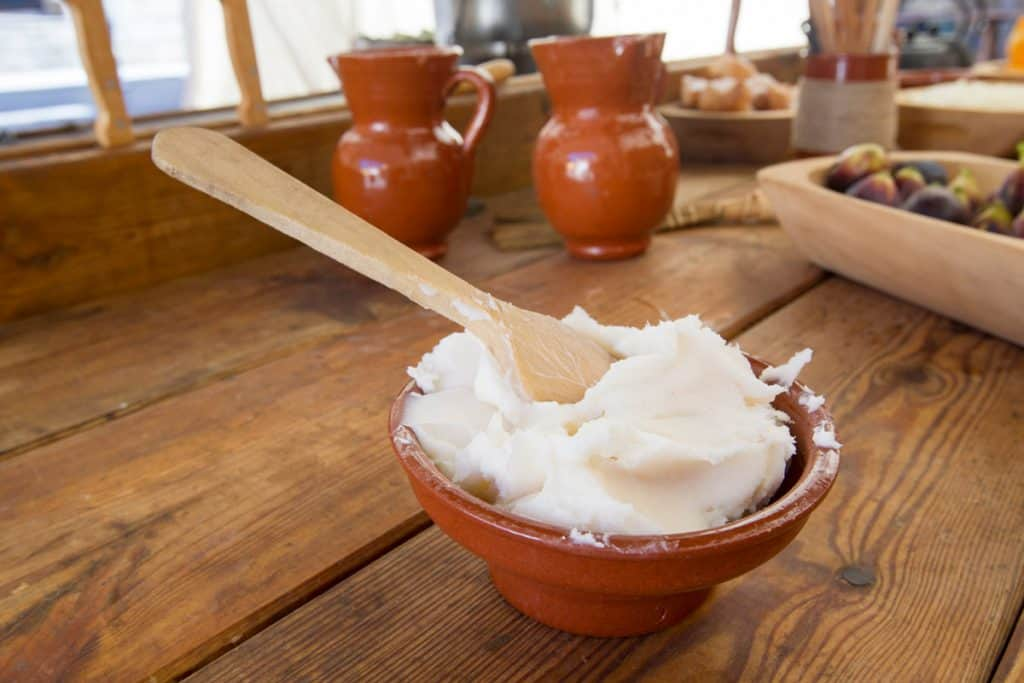 A bowl filled with solid lard sitting on a wooden counter top.