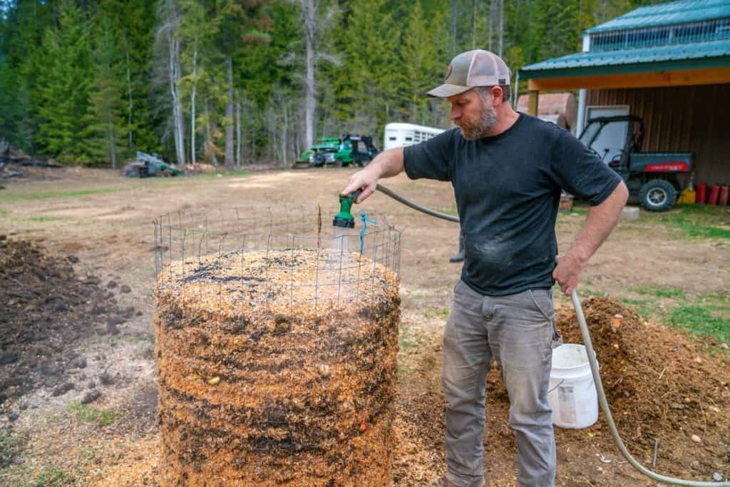 A man watering a large wire compost bin filled with layers for compost.