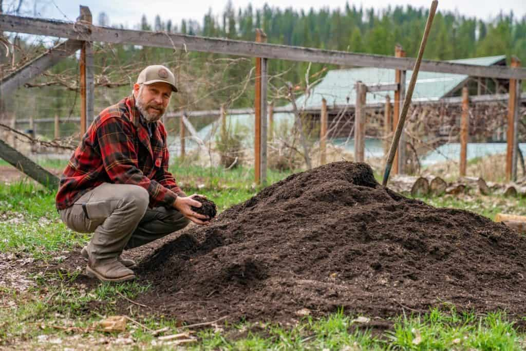 A man kneeling by a large pile of finished compost.