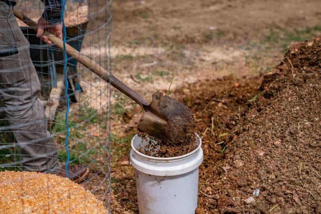 A shovel adding compost materials to a five gallon bucket.