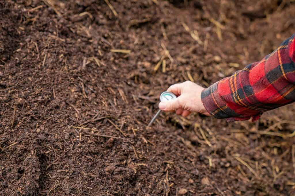 A hand placing a compost thermometer into a pile of compost.
