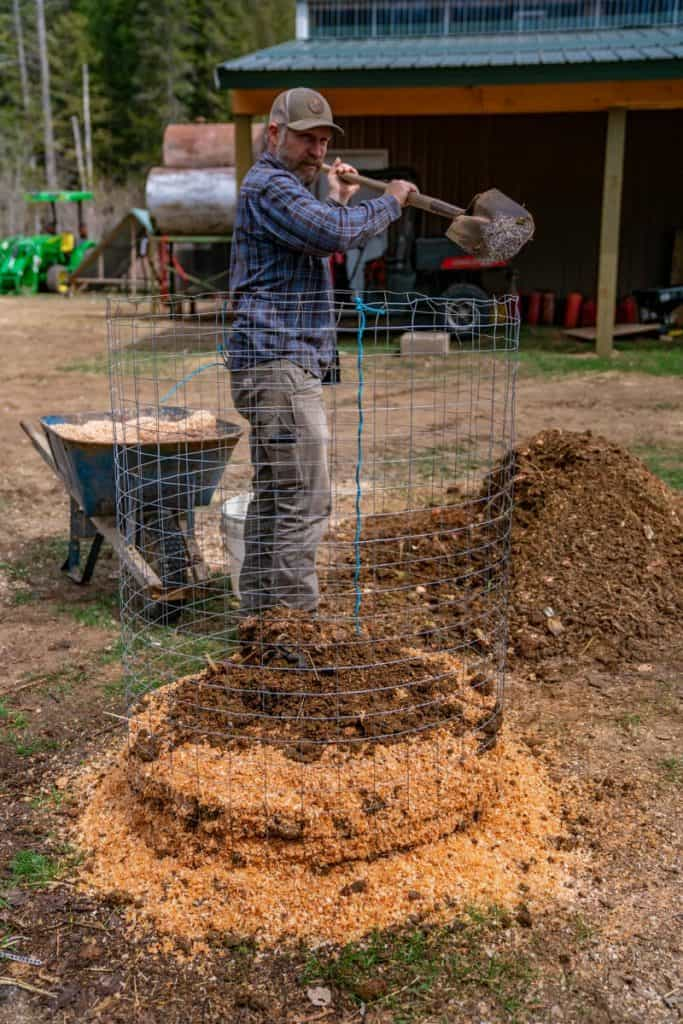 A man layering compost materials and wood chips in a wire bin.