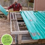 Pinterest pin on using chickens to restore the land using a mobile chicken coop. Image of a man fixing up a mobile chicken coop.