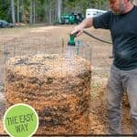 Pinterest pin for how to make compost the easy way at home. Image of a man watering a large bin of compost.