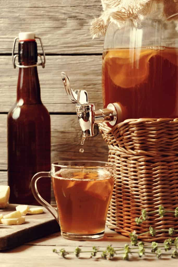 A continuous brew kombucha set up with a glass being filled.