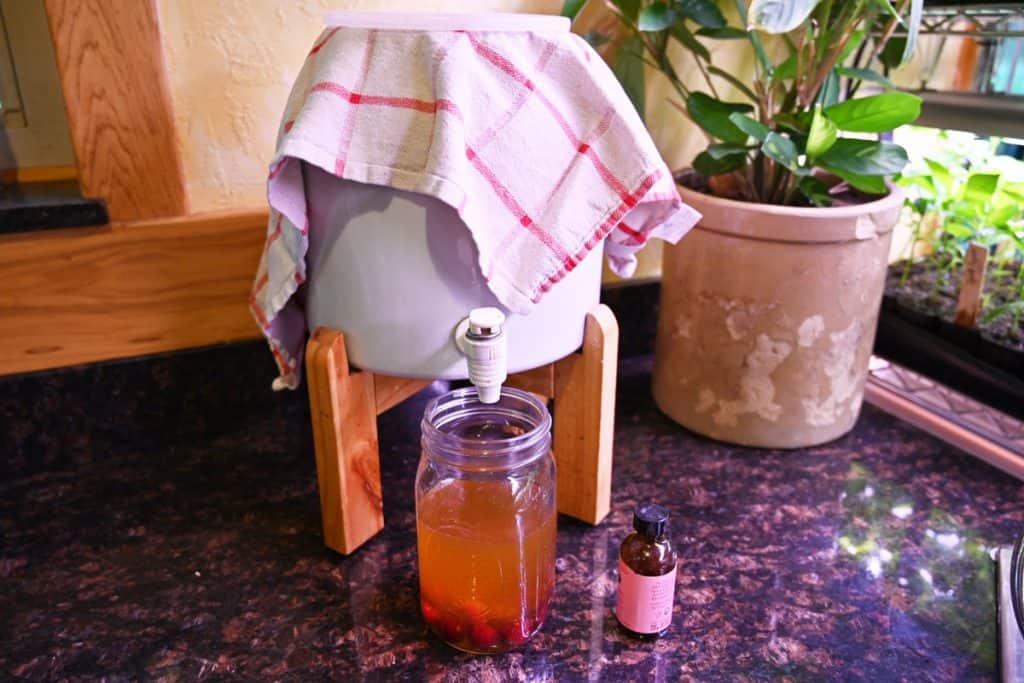 Continuous brew kombucha system pouring kombucha into a mason jar.