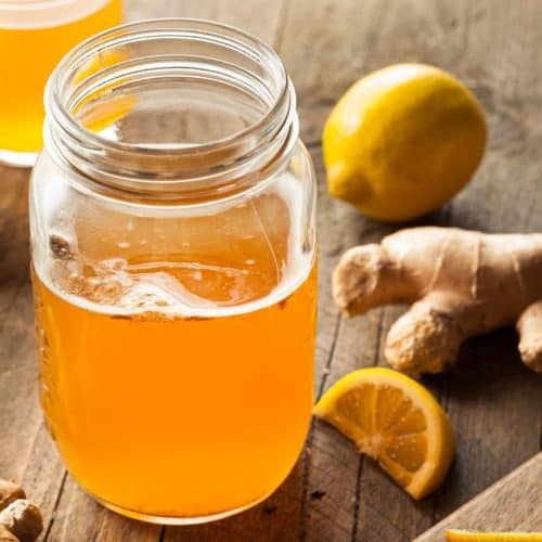 A mason jar filled with kombucha with lemons and fresh ginger sitting on the table next to the glass.