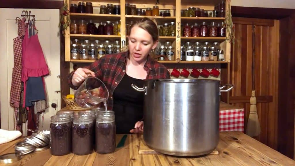 A woman adding water to top off a jar of black beans before canning.