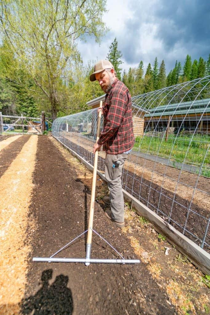 A man raking a long garden bed row to smooth the soil.