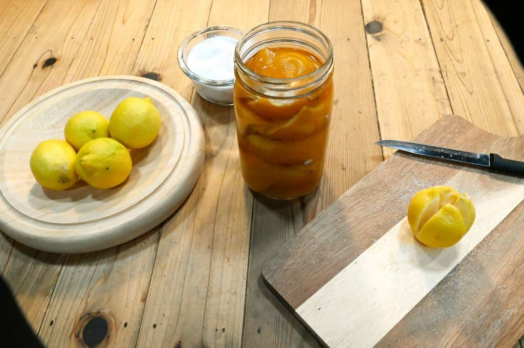 A jar of preserved lemons next to a plate of fresh lemons and a cutting board with a salted lemon.