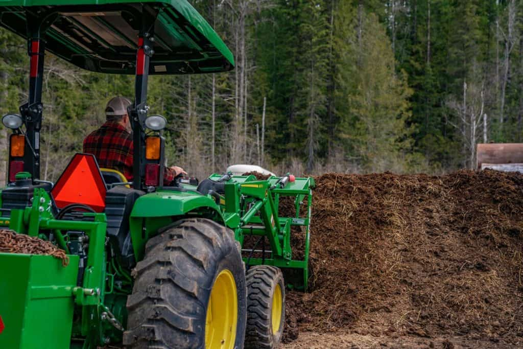 A large tractor turning a large compost pile.