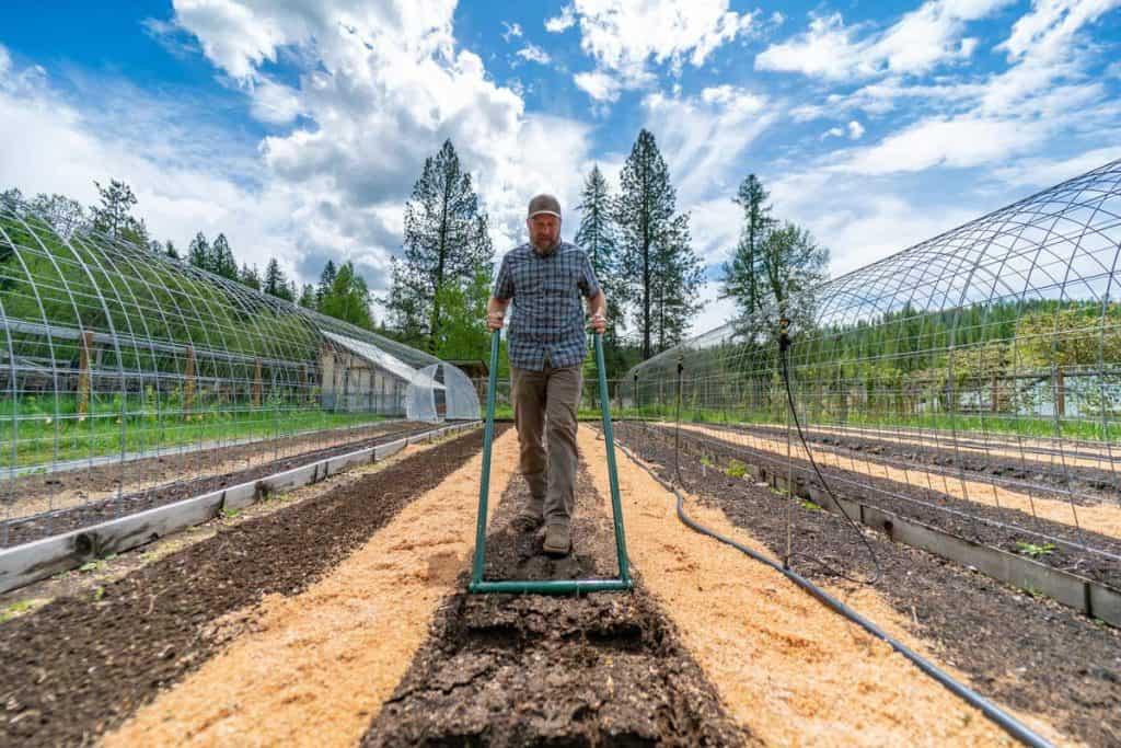 A man loosening a garden row with a broadfork.