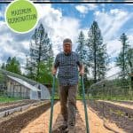 Pinterest pin for how to grow carrots from seed for maximum germination. Photo of a man preparing the garden bed with a broadfork.